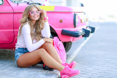Stylish girl with denim jacket near the pink car with a pink bag Photo