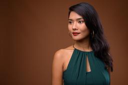 Studio shot of beautiful Asian businesswoman against brown backg Photo