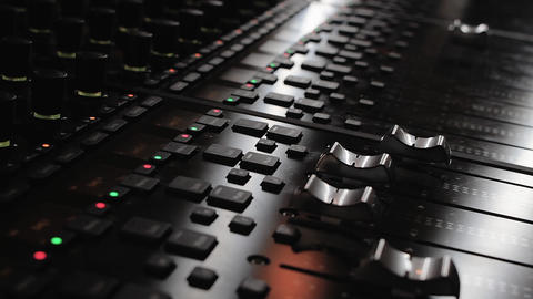 Sound engineer hand adjusting levels on a mixing console Footage