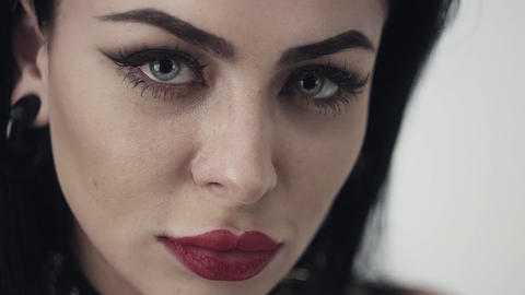 Face of cute girl with sexy lips, big blue eyes, long black hair and makeup Live Action