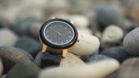 Luxury black Watch with black watch strap on the beach stones Live Action