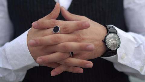 Crossed fingers close up of stylish man in a white shirt. Stylish watch on the Live Action