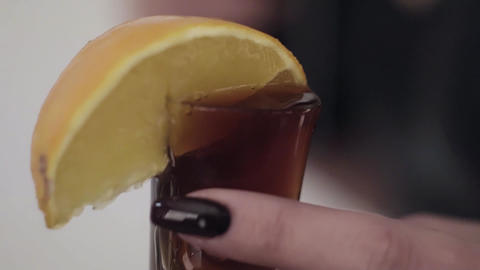 Brown liquid is being poured on glass with lemon held by female's hand Archivo