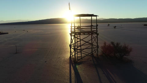Aerial drone scene of sillhuete of wooden lookout tower at plane desert, sunset. Golden hour sun Footage