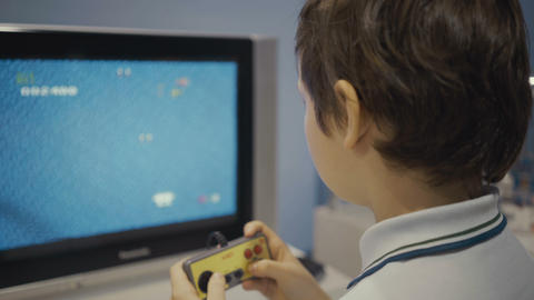 Happy young boy using a retro controller to play a video game Footage