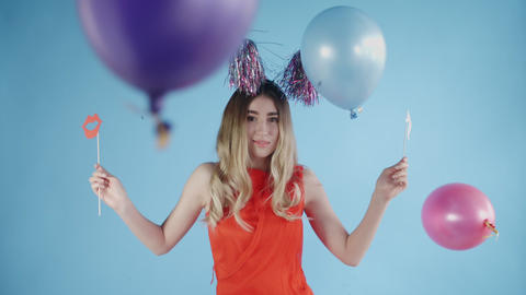 Beautiful girl in party hat are dancing under falling confetti and Balloons on a Live Action