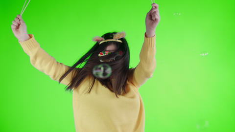 Beautiful young woman with funny hat and glasses is dance alone on a green Footage