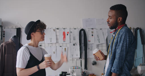 Designers man and woman relaxing talking drinking take-out coffee in studio Archivo