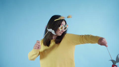 Beautiful young woman with funny hat and glasses is dance alone on a blue Footage