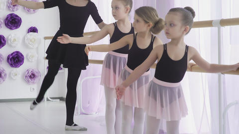 Little girls are having classical ballet lesson learning leg movements with Footage