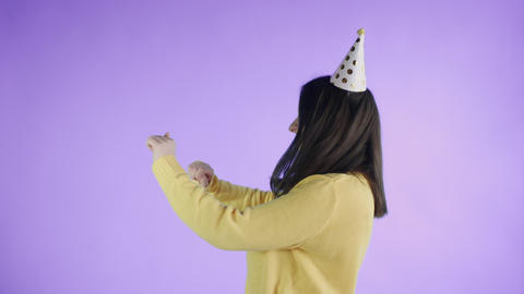 Young woman in yellow sweater with party hat is dancing on a purple background Footage