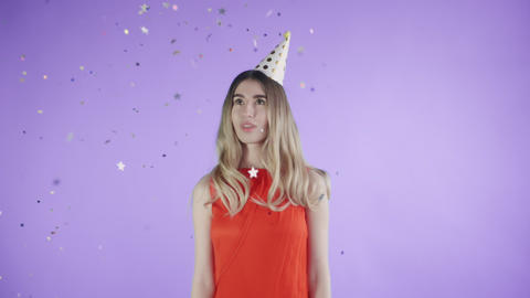 Beautiful girl in party hat are standing under confetti on a purple background Footage
