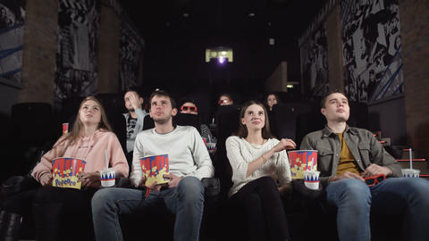 Young people laugh at comedy movie in cinema theatre. Young people laughing at Footage