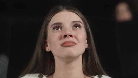 Woman at the cinema beings to cry while watching a sad and emotional movie Footage