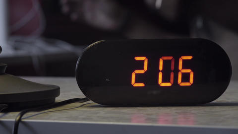 Black plastic electronic digital clock indicates time in orange color on table Footage