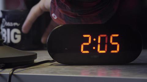 Black rectangular shaped electronic digital clock shows time in orange color Footage