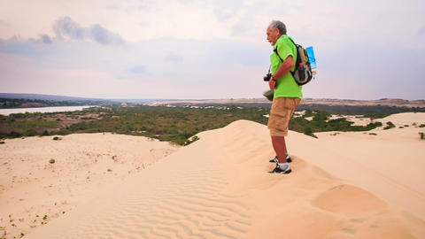 Old Man Sits down on Crest Cries with Joy in White Sand Dunes Footage