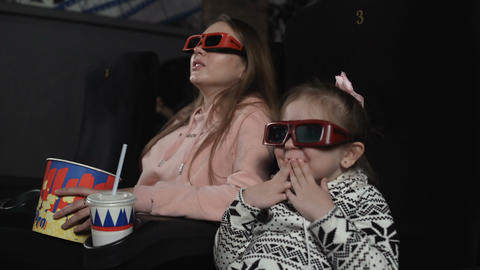 Mother with her daughter are watching 3d film in cinema. Emotion - surprise Footage