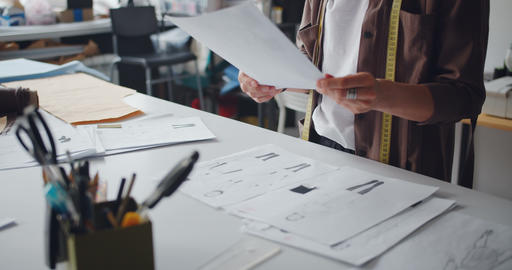 Clothes designer holding drawings of clothes working in studio creating garments Live Action