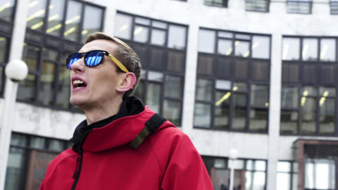 Portrait of guy in red sport clothes and sunglasses sings on winter day outside Footage