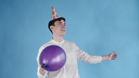 Young man in party hat is dancing under Balloons on a blue background Footage