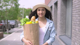 A young attractive woman in a denim jacket and hat carries a grocery bag while Footage