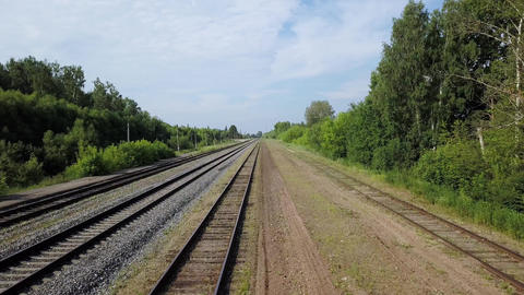 Sunny scenery of empty long railways laying along green line of bushes and trees Footage