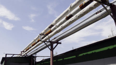 Industrial pipelines and tubes are laying outside and around big factory area Footage