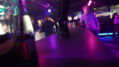 Dancer girl feet in hight heels twists on bar deck at night club party Footage