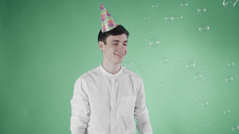 Young man with party hat is surprised flying bubbles on a green background Footage