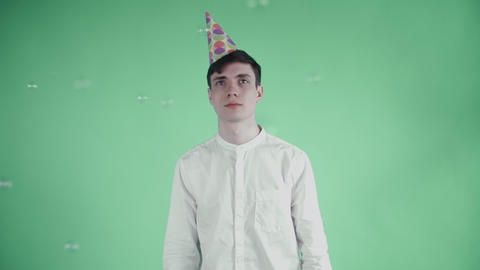 Young man in party hat are standing under soap bubble on a green background Footage