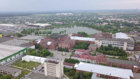 Scenery of large plant area, buildings, houses, trees, lake, streets in big city Footage