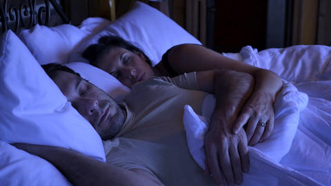 Woman smiling and waking up her husband affectionately at night while lying in bed Footage