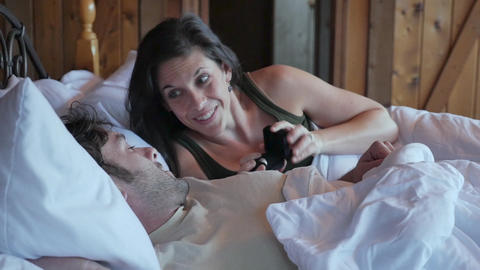 Woman showing a ring to a man lying next to her in bed as if she is preposing to him in slow motion Live Action