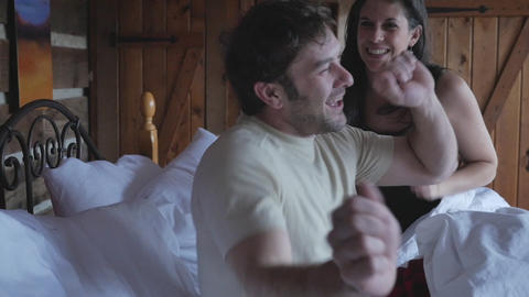 Happy young couple in their early 30s laughing and tickling each other in a bedroom bed in slow Footage