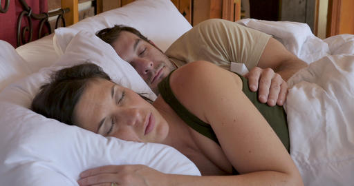 Man happily waking up and cuddling with a woman in bed rubbing her arm, holding her hand and showing Live Action