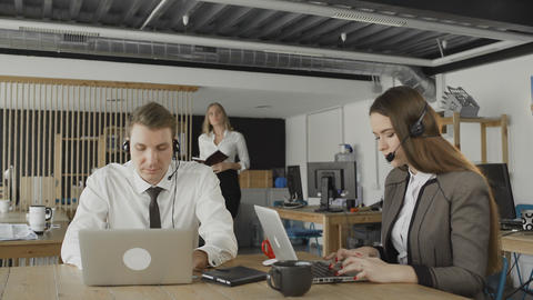 Customer service operators taking calls in busy call... Stock Video Footage