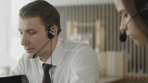 Close up of customer service operators taking calls in busy call center Footage