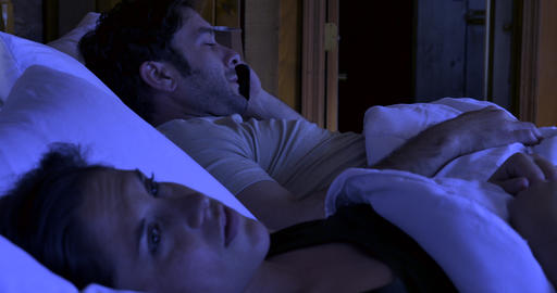 Man trying to get off the phone while his wife is annoyed trying to sleep at night in bed Footage