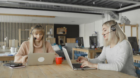 Women with headphones with microphone talks to a customers via computer. Women Footage