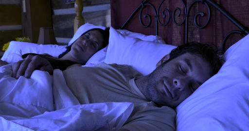 Happy young attractive couple in their early 30s or late 20s getting a good nights sleep in a cozy Footage