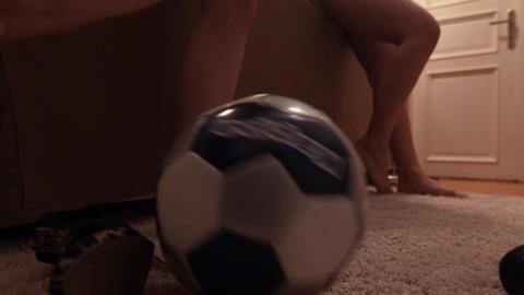 Young girls kicks football barefeet in living room on furry rug carpet Footage