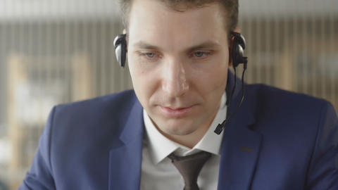 Businessman in suit wear headset talking looking at laptop making notes, male Live Action