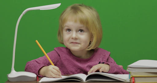 Girl drawing at the table. Education process in classroom. Chroma Key Footage