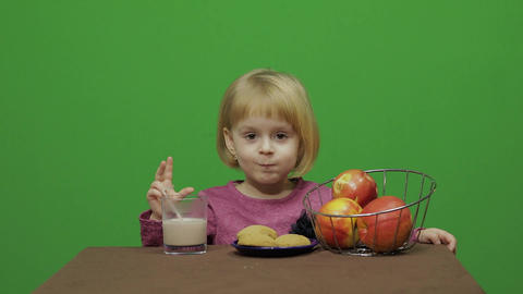 Girl sitting at the table and eating chocolate, cookies…, Live Action