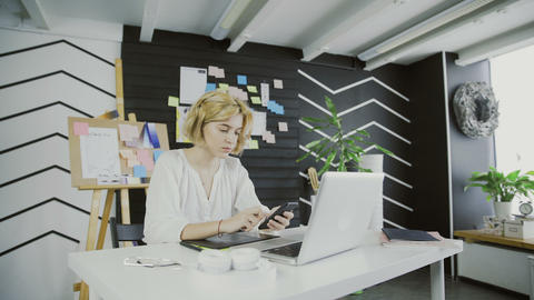 Attractive female designer holding smartphone sitting in office Footage