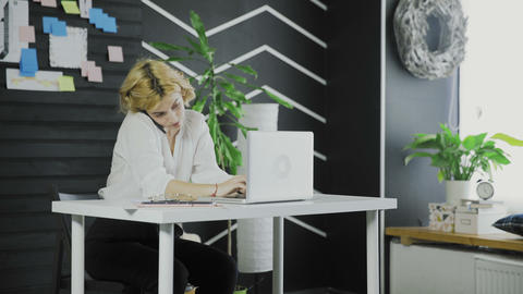 Attractive business woman talking on the cell phone while typing on laptop Footage