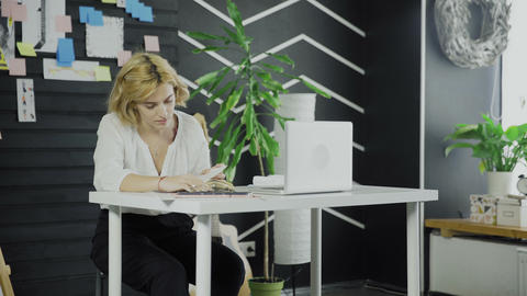 Pretty girl sitting and reading book in office Footage
