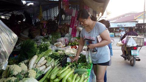 Sukhothai, Thailand - 2019-03-06 - Vegetable Market Vendor Makes Sale of Zuchini Footage