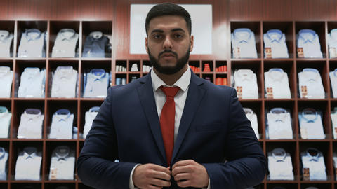 Businessman looking at the camera and choosing classical suit in the suit shop Live Action
